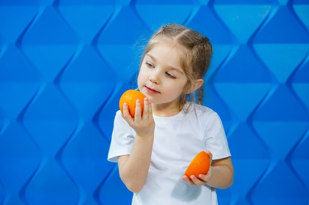 Menina loira muito bonita em uma camiseta branca sorri sobre um fundo azul. criança bonita elegante tem meia laranja nas mãos. o conceito de um retrato emocional.