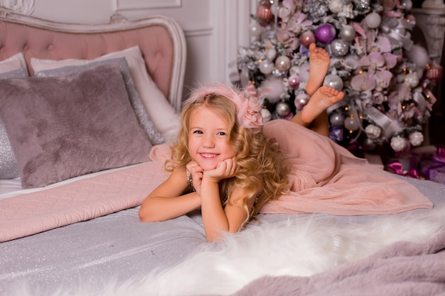 Menina loira na cama ao lado da árvore de natal. véspera de natal