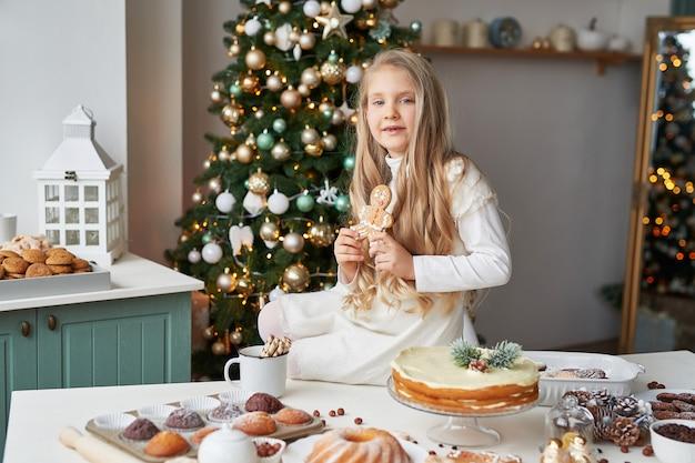 Menina loira na cozinha do ano novo com cupcakes e doces