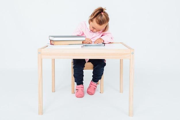 Menina loira na escola, sorrindo, sentada em uma cadeira ao lado de uma mesa com livros pintando