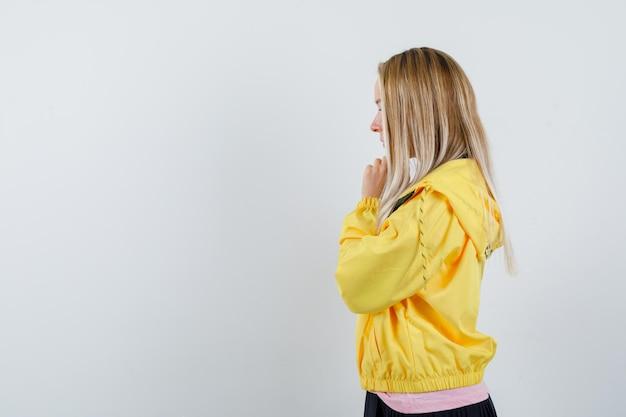 Menina loira na jaqueta amarela, apertando as mãos em gesto de oração e olhando esperançosa.