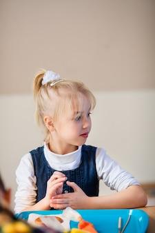 Menina loira na oficina de decoração de gengibre