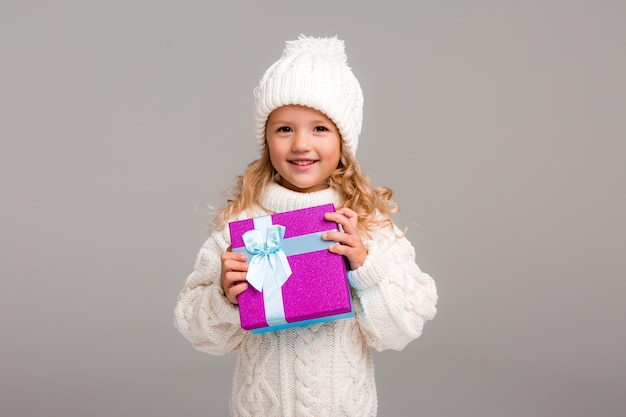 Menina loira no chapéu de inverno sorrindo segurando uma caixa de presente