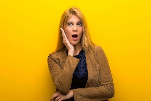 Menina loira no fundo amarelo vibrante surpreso e chocado ao olhar para a direita