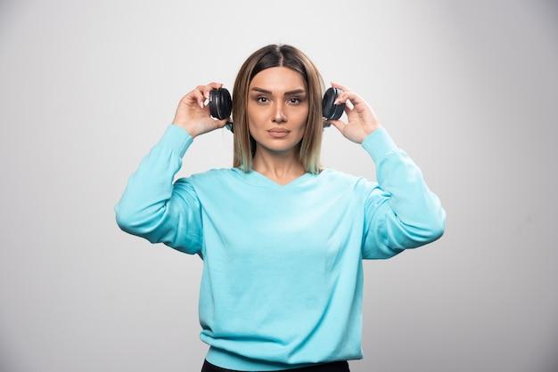 Menina loira no moletom azul segurando fones de ouvido e se prepara para usá-los para ouvir a música.