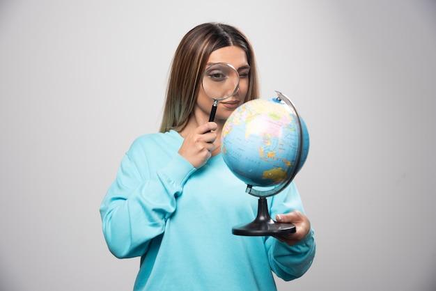 Menina loira no moletom azul segurando um globo e procurando um destino com lupa.