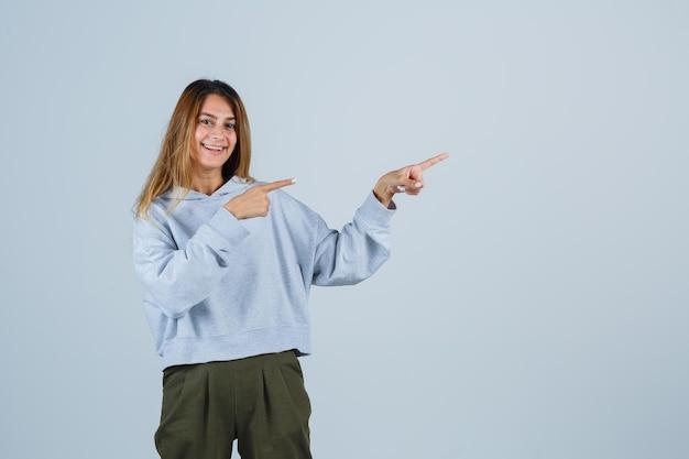 Menina loira no moletom azul verde oliva e calças apontando para a direita com o dedo indicador e olhando encantadora, vista frontal.