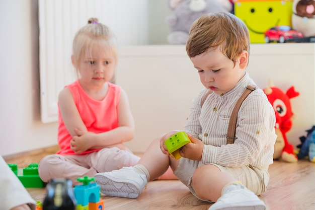 Menina loira olhando o menino brincando