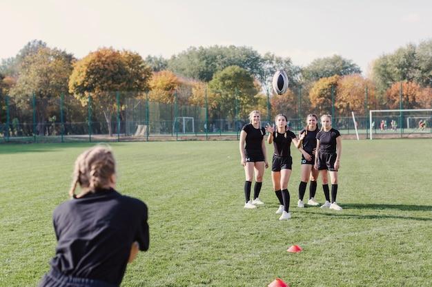 Menina loira passando uma bola de futebol