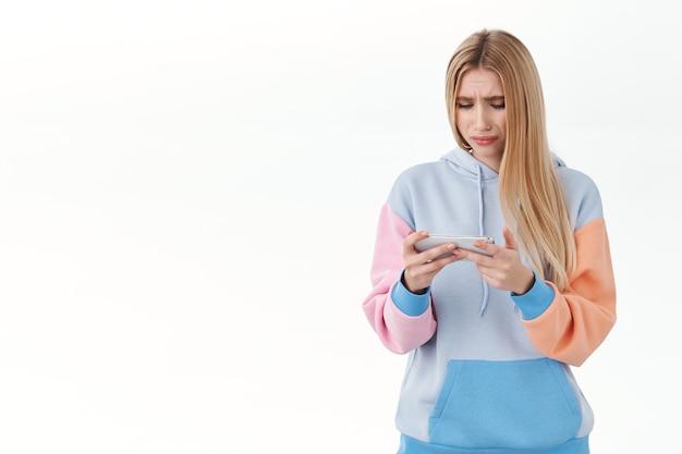 Menina loira pensativa e chateada se sentindo desconfortável com o fracasso, assistindo a um filme triste no celular