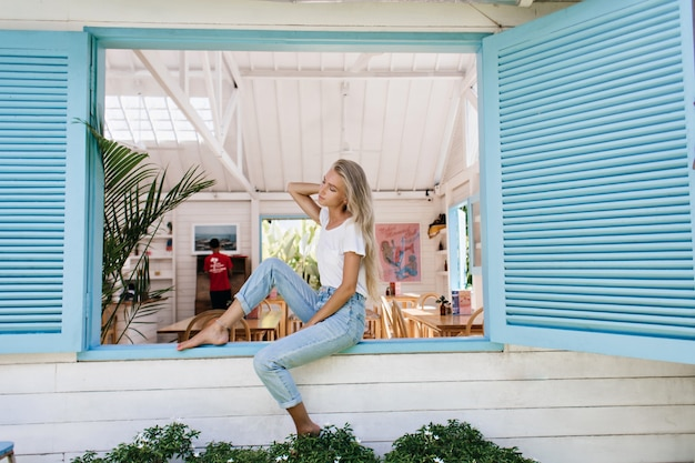 Menina loira pensativa em camiseta casual, sentada no peitoril da janela. retrato de um sonho modelo feminino branco em calças jeans fazendo pose de manhã.