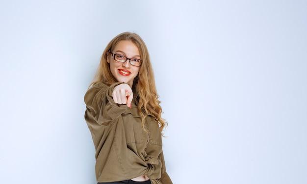 Menina loira percebendo e apontando para a pessoa à frente.