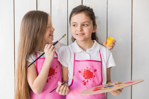 Menina loira pintando na bochecha do amigo com pincel