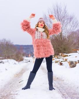 Menina loira posando com uma jaqueta de pele rosa, botas de inverno e um chapéu roxo na neve. caminhando em um caminho cheio de neve, estilo de vida