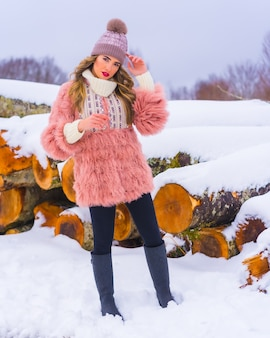 Menina loira posando com uma jaqueta de pele rosa e um chapéu roxo na neve. ao lado de algumas árvores cortadas com gelo, estilo de vida de inverno