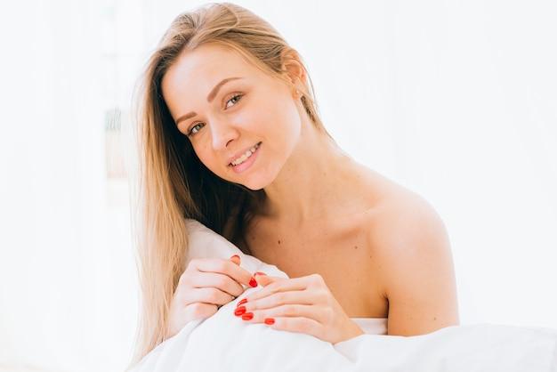 Menina loira posando na cama