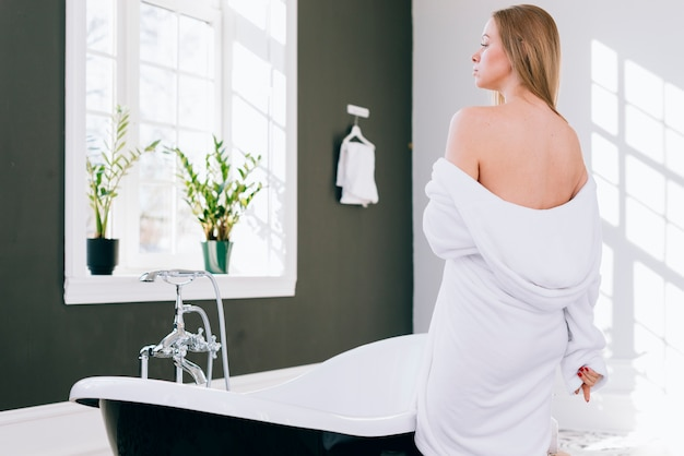 Menina loira posando no banheiro com roupão de banho