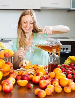 Menina loira positiva que derrama bebidas frescas