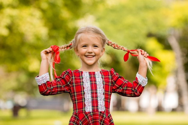 Menina loira primeira série vestido xadrez vermelho sorrindo na rua