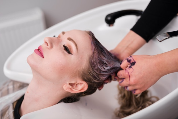 Menina loira, recebendo seu cabelo lavado