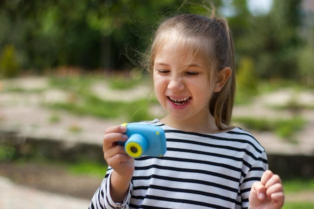 Menina loira rindo no parque em um dia ensolarado segurando uma pequena câmera, tirando fotos, olhando para ela