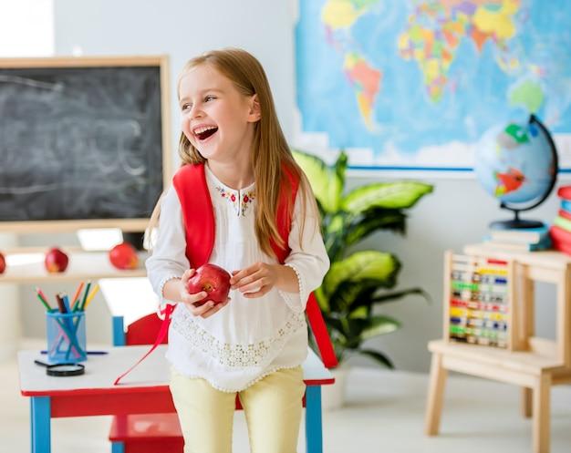 Menina loira rindo segurando uma maçã na sala de aula de escola