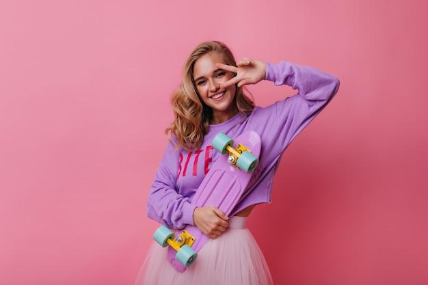 Menina loira romântica posando com símbolo da paz em rosado. mulher encantadora e encaracolada segurando o skate rosa e rindo.