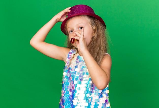 Menina loira satisfeita com chapéu de festa roxo, soprando apito de festa e colocando a mão no chapéu isolado na parede verde com espaço de cópia