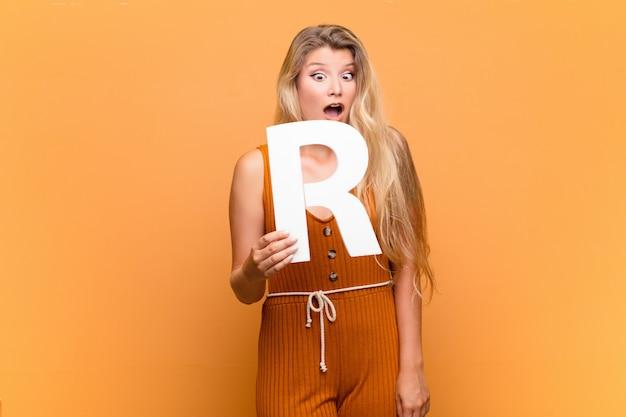 Menina loira segurando a letra r