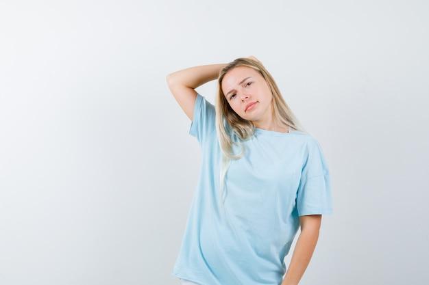 Menina loira segurando a mão na cabeça em t-shirt azul e olhando sério, vista frontal.