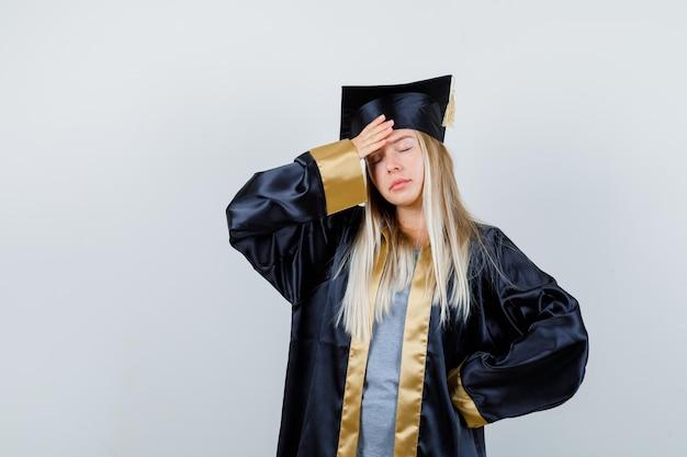 Menina loira segurando a mão na cintura enquanto colocava a mão na testa com um vestido de formatura e boné e parecendo cansada