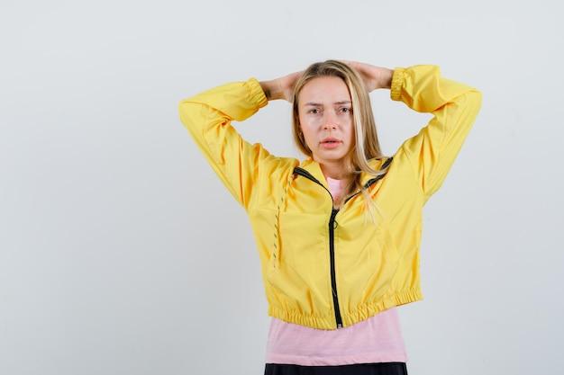 Menina loira segurando as mãos atrás da cabeça em uma jaqueta amarela e parecendo triste.