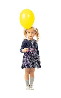 Menina loira segurando ballon amarelo