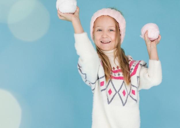 Menina loira segurando bolas de neve