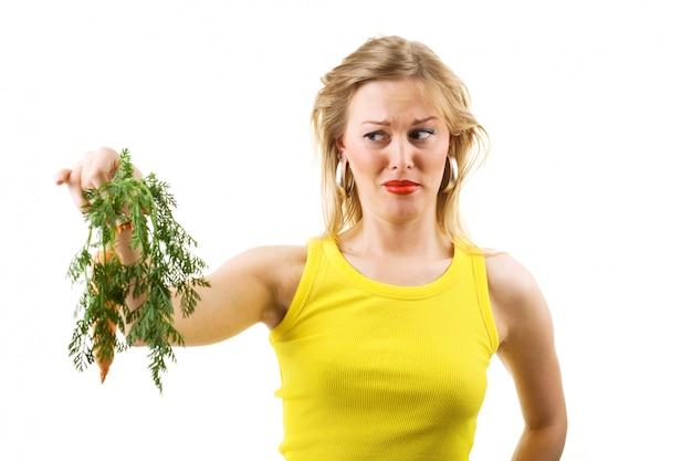Menina loira segurando cenoura podre