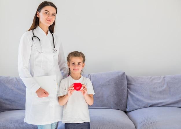 Menina loira segurando coração com médico