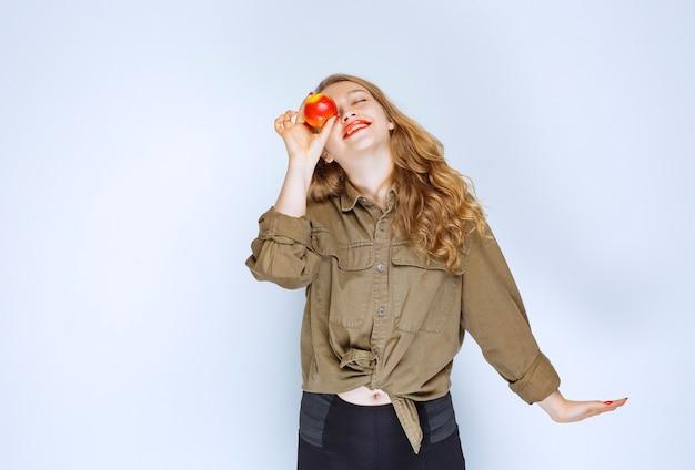 Menina loira segurando e promovendo um pêssego vermelho.
