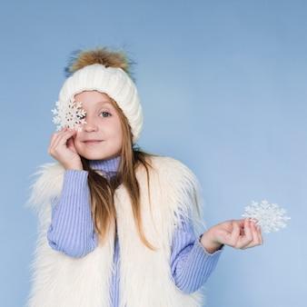Menina loira segurando flocos de neve