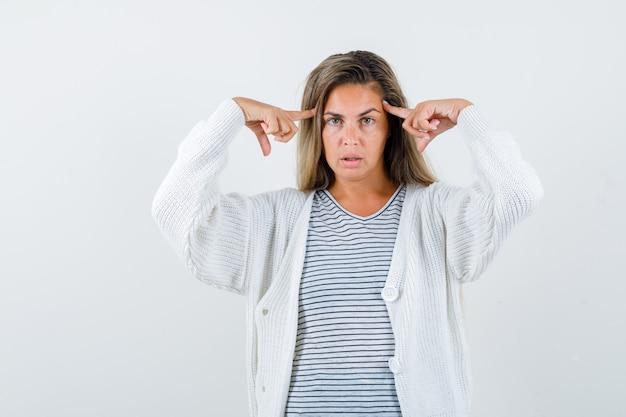 Menina loira segurando os dedos indicadores nas têmporas em uma camiseta listrada, casaco de lã branco e calças jeans e parecendo atraente. vista frontal.