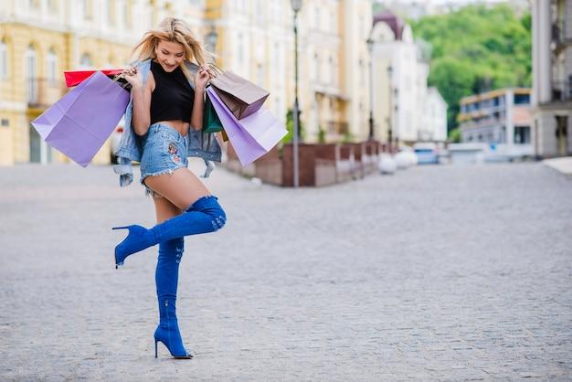 Menina loira segurando sacolas de compras posando