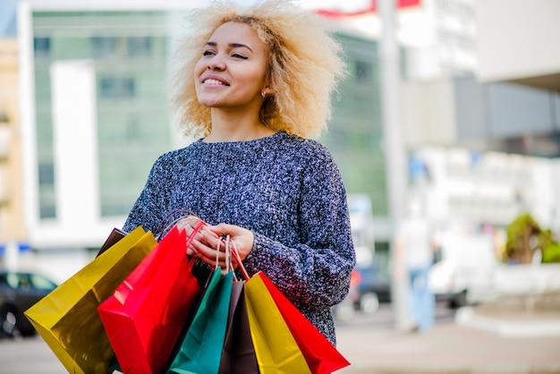 Menina loira segurando sacolas de compras sorrindo