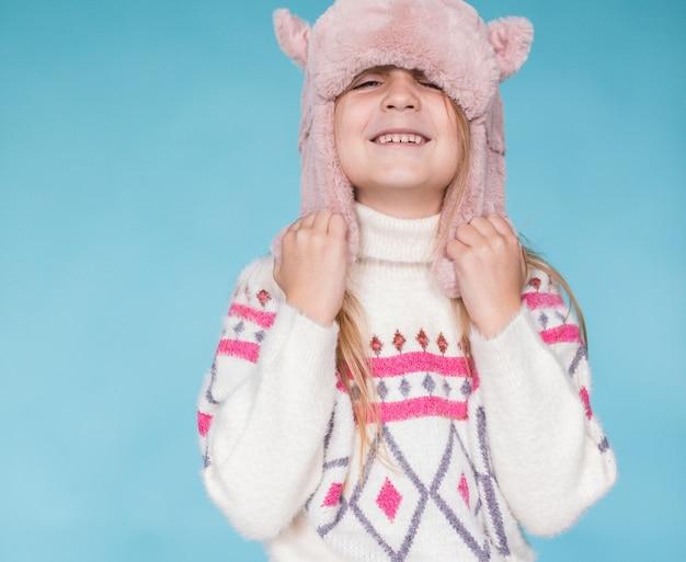 Menina loira segurando seu chapéu de inverno