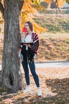 Menina loira segurando um caderno e tomando café