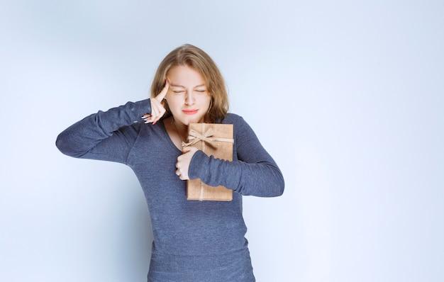 Menina loira segurando uma caixa de papelão e tendo uma ideia.