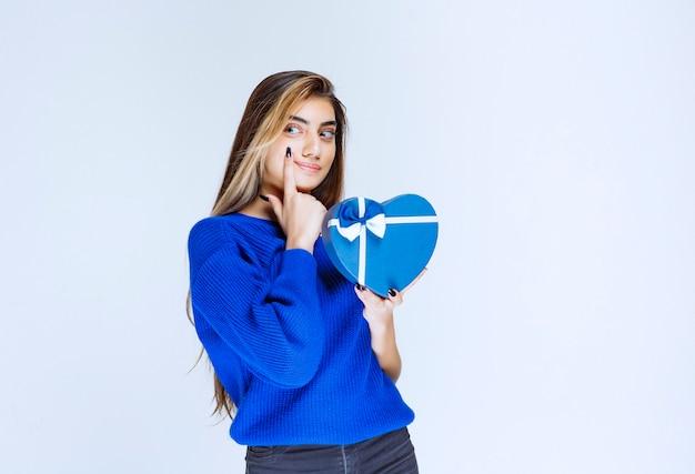 Menina loira segurando uma caixa de presente de forma de coração azul e pensando.