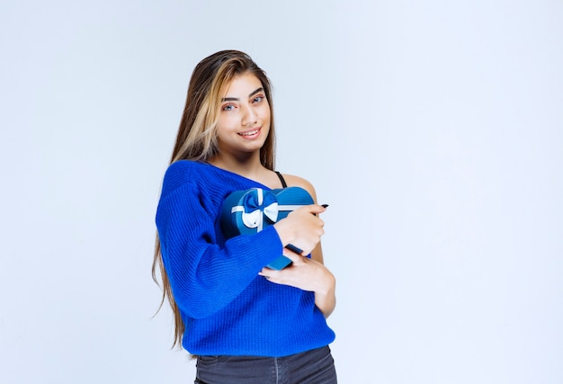 Menina loira segurando uma caixa de presente em forma de coração azul.