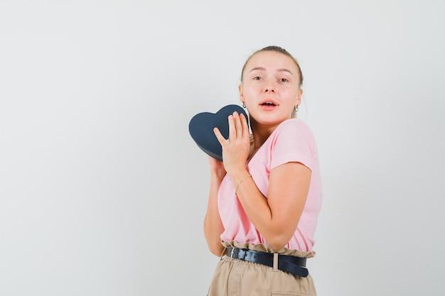 Menina loira segurando uma caixa de presente em t-shirt, calças e olhando feliz, vista frontal.