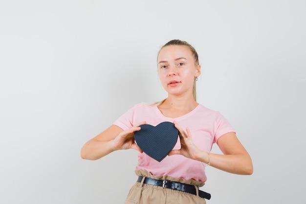 Menina loira segurando uma caixa de presente em t-shirt, calças e parecendo confiante, vista frontal.