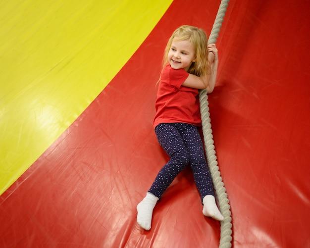 Menina loira segurando uma corda