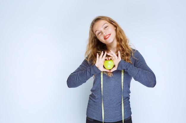 Menina loira segurando uma maçã verde nas palmas das mãos.